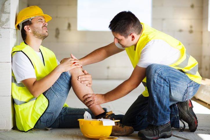 Injured construction worker being attended to by co-worker
